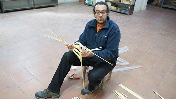 Al taller, explicant com es treballa la palma. Foto: Carles X. Cabós.
