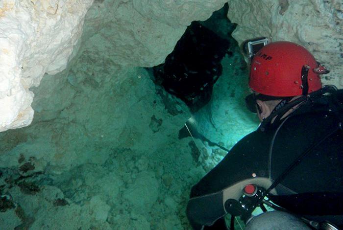 Esperant torn per passar per una restricció (lloc molt estret per on només passa un bussejador amb dificultat) a la cova de El Chicho (República Dominicana). Foto: Cedida.